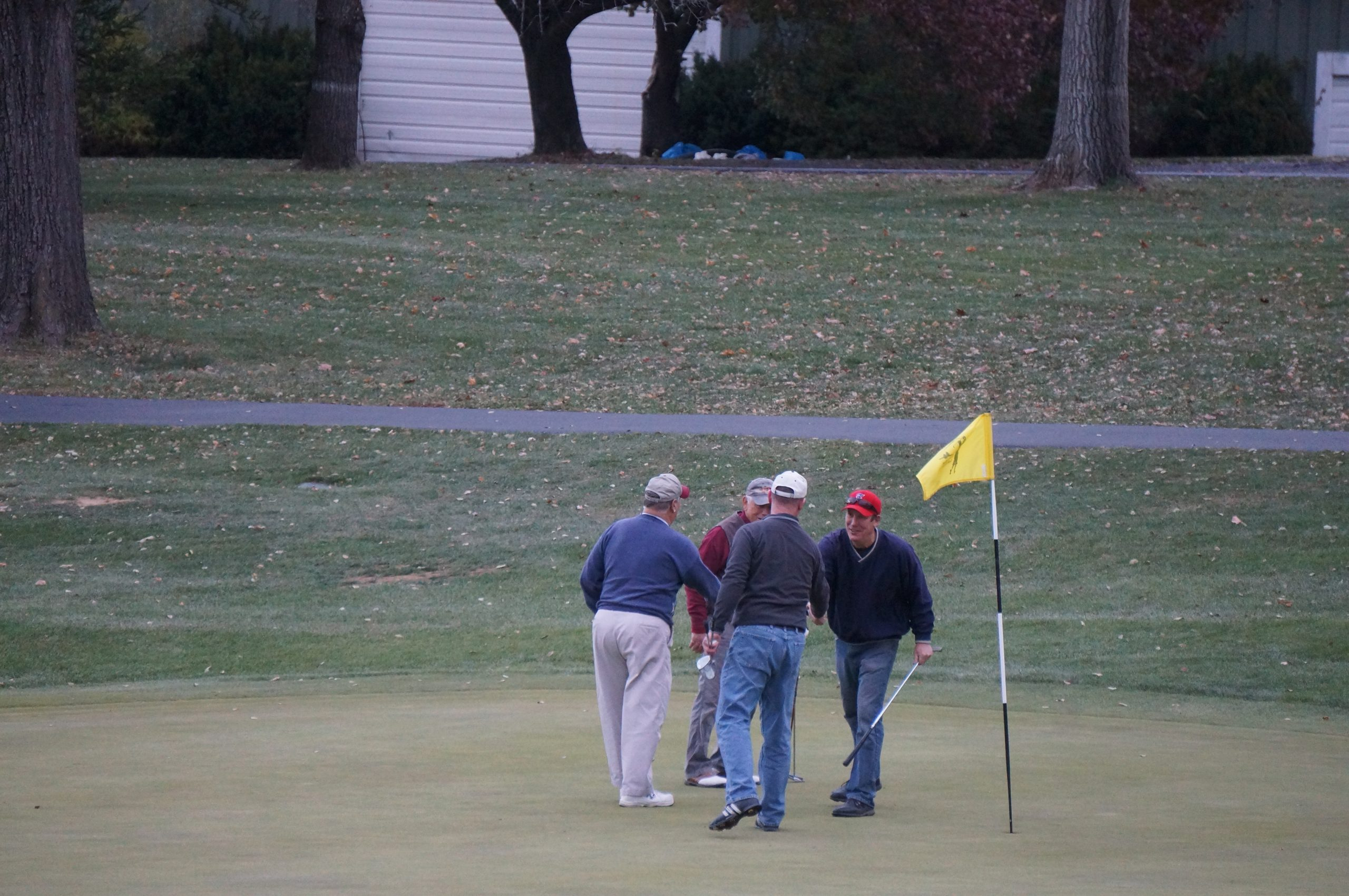 men shaking hands near golf hole