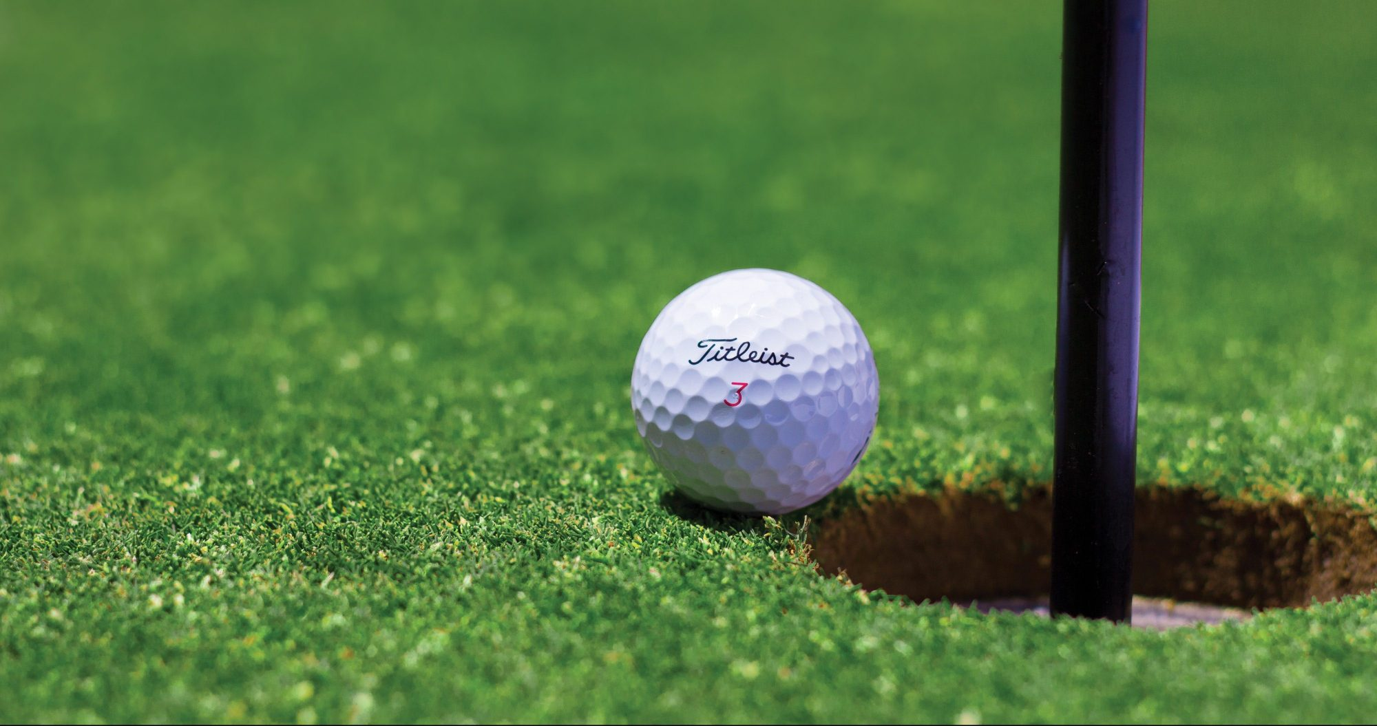 golf ball on edge of golf hole